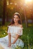Portrait of beautiful sensual brunette girl in white dress sitti Stock Image
