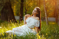 Portrait of beautiful sensual brunette girl in white dress sitti Stock Photo