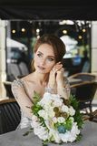Portrait of beautiful and sensual brunette model girl with bright makeup and blue eyes in fashionable lace dress sitting at a tabl royalty free stock image