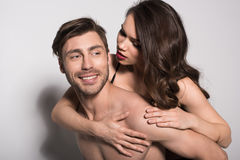 Portrait of beautiful sensual couple, man giving woman piggyback ride stock photography