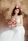 Portrait of beautiful sensual girls brunette in white lace dress. With a wreath of flowers on his head, sitting on the couch Stock Photography