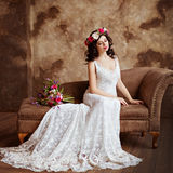 Portrait of beautiful sensual girls brunette in white lace dress. With a wreath of flowers on his head, sitting on the couch and looking down Stock Photography
