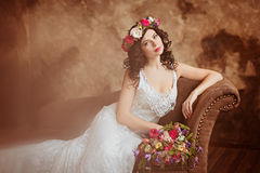 Portrait of beautiful sensual girls brunette in white lace dress. With a wreath of flowers on his head, sitting on the couch Stock Photo