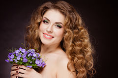 Portrait of a beautiful sensual redheaded girl with flowers in t. Heir hands, smiling happily in the Studio on a dark background Stock Images