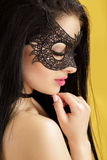 Portrait of beautiful sensual woman in black lace mask on yellow background. girl in venetian mask royalty free stock image