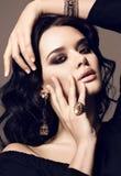 Portrait of beautiful sensual woman with dark hair with bijou. Fashion studio photo of beautiful sensual woman with dark hair and bright makeup,with bijou Royalty Free Stock Images