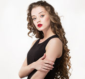 Portrait of a beautiful sensuality woman in black dress with long curly hair. And red lipstick posing pointing hand finger over white background Stock Images