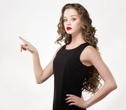 Portrait of a beautiful sensuality woman in black dress with long curly hair. And red lipstick posing pointing hand finger over white background Stock Photo