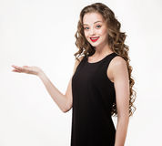 Portrait of a beautiful sensuality woman in black dress with long curly hair. And red lipstick posing pointing hand finger over white background Stock Photography