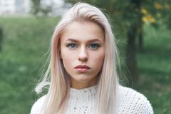 Portrait of a beautiful serious blonde girl in a white knitted sweater. Portrait of a beautiful serious blonde girl in a white knitted sweater royalty free stock images