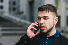 Portrait of beautiful and serious young businessman talking on the phone against the backdrop of modern architecture Stock Photography