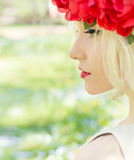 Portrait of beautiful sexy blonde girl with a wreath of peony walks in the garden on a sunny day Royalty Free Stock Images