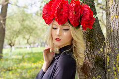 Portrait of beautiful sexy blonde girl with a wreath of peony walks in the garden on a sunny day Royalty Free Stock Image