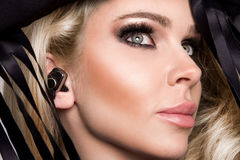 Portrait of the beautiful sexy blonde with a perfect face which is in the ear headphones and listen to music Royalty Free Stock Photo
