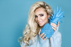 Portrait beautiful, blonde woman in blue sweater and holding a blue pineapple. Portrait beautiful, blonde woman in blue sweater, standing on a blue background stock image