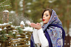 Portrait of beautiful sexy brunette girl in a blue scarf on the. Background of nature in winter blowing on snowflakes in her hands, close-up Royalty Free Stock Image
