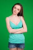 Portrait of beautiful brunette girl  wearing shorts over green b Royalty Free Stock Photo