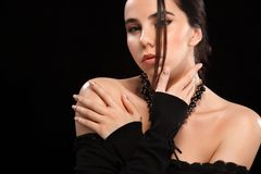 Portrait of beautiful brunnete girl, on black background. Pretty girl model. A brunette woman in a black dress. stock photography