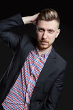 Portrait of beautiful brutal men on a dark background. Blonde with beautiful shiny hair. A businessman, a Manager. Portrait of beautiful brutal man on a dark royalty free stock image