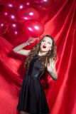 Portrait of a beautiful elegant girl brunette with long hair in evening dress with bright festive makeup and red lipstick. With red balloons on a red background royalty free stock images