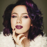 Portrait of beautiful fashion model with purple hair over g. Rey background royalty free stock photo