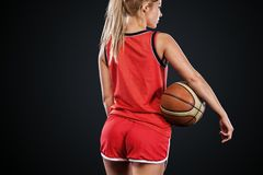Portrait of a beautiful and girl with a basketball in studio. Sport concept isolated on black background. Portrait of a beautiful and girl with a basketball in royalty free stock images