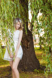 Portrait of a beautiful girl with big full lips, with white hair in a white dress near a tree stock image