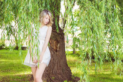 Portrait of a beautiful sexy girl with big full lips, with white hair in a white dress near a tree Stock Photo