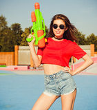 Portrait beautiful sexy girl posing in denim shorts, white T-shirt and sunglasses in the skate park with water gun on a warm summe Royalty Free Stock Photo