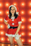 Portrait of beautiful girl wearing santa claus clothes on red background stock image