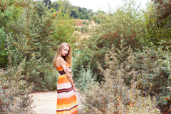 Portrait of beautiful sexy girls with full lips and blond hair stands near the lake with bushes of sea-buckthorn in long dress Stock Photos