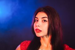 Portrait of beautiful traditional oriental belly dancer girl on blue neon smoky background. Woman in red exotic royalty free stock image