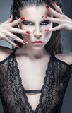 Fashion women. Portrait of a beautiful sexy woman with makeup and manicure on a dark background. Glamour picture Royalty Free Stock Images