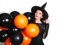 Portrait of beautiful young woman in black witch halloween costume with orange and black balloons over white background royalty free stock photo