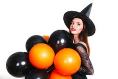 Portrait of beautiful young woman in black witch halloween costume with orange and black balloons over white background Royalty Free Stock Photos