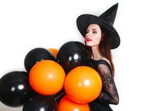 Portrait of beautiful young woman in black witch halloween costume with orange and black balloons over white background Royalty Free Stock Image