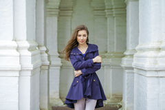 Portrait of a beautiful young woman in dark blue coat royalty free stock photography