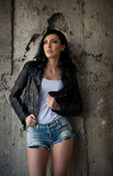 Portrait of beautiful young woman with jeans,white undershirt black leather jacket , in urban background. Attractive brunette with perfect long legs on high royalty free stock photos