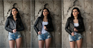 Portrait of beautiful sexy young woman with jeans,white undershirt  black leather jacket , in urban background. Stock Photos
