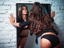 Portrait of beautiful sexy young woman looking into mirror. Rear view Stock Image