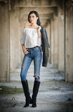 Portrait of beautiful sexy young woman with modern outfit, leather jacket, jeans, white blouse and black boots Stock Photos