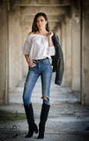 Portrait of beautiful sexy young woman with modern outfit, leather jacket, jeans, white blouse and black boots Stock Photo