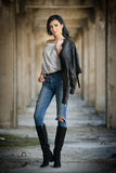 Portrait of beautiful sexy young woman with modern outfit, leather jacket, jeans, white blouse and black boots Royalty Free Stock Photos