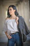 Portrait of beautiful young woman with modern outfit, leather jacket, jeans, white blouse and black boots Royalty Free Stock Images