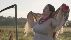 Portrait of beautiful plump woman with a scythe putting shawl on her head in sunlight on the green summer field. Portrait of beautiful Slavic overweight woman stock video footage