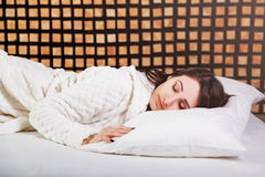 Portrait of a beautiful sleeping girl brunette on a white bed. Stock Image