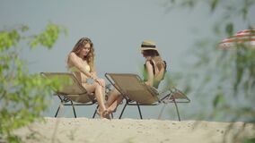 Portrait of beautiful slim tanned women applying sunscreen on sunny summer resort. Two gorgeous Caucasian female