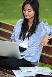 Portrait of a beautiful smart asian female student studying. With laptop computer while sitting on the bench at the park Stock Photo