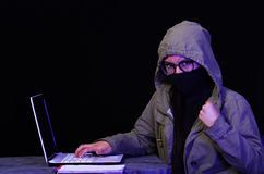 Portrait of a beautiful and smart girl hacker with laptop on dark background using glasses and covering her neck, mouth Royalty Free Stock Photos