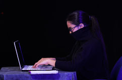 Portrait of a beautiful and smart girl hacker with laptop on dark background using glasses and covering her neck, mouth Stock Images